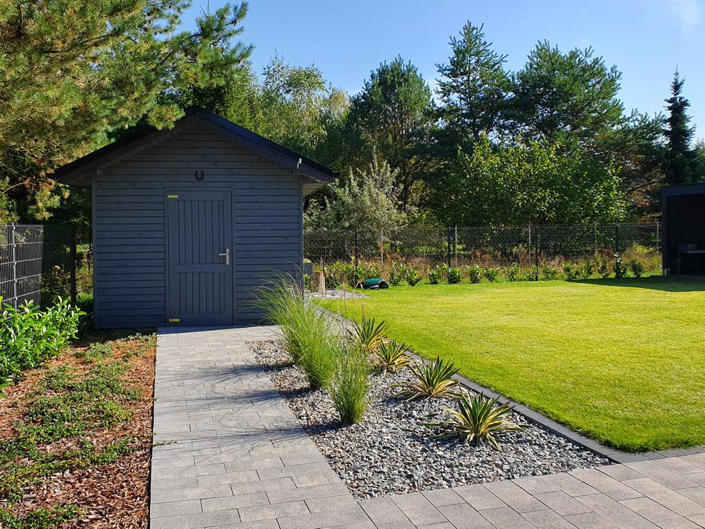 Ogród minimalistyczny. Pomieszczenie gospodarcze wśród nasadzeń z traw ozdobnych.